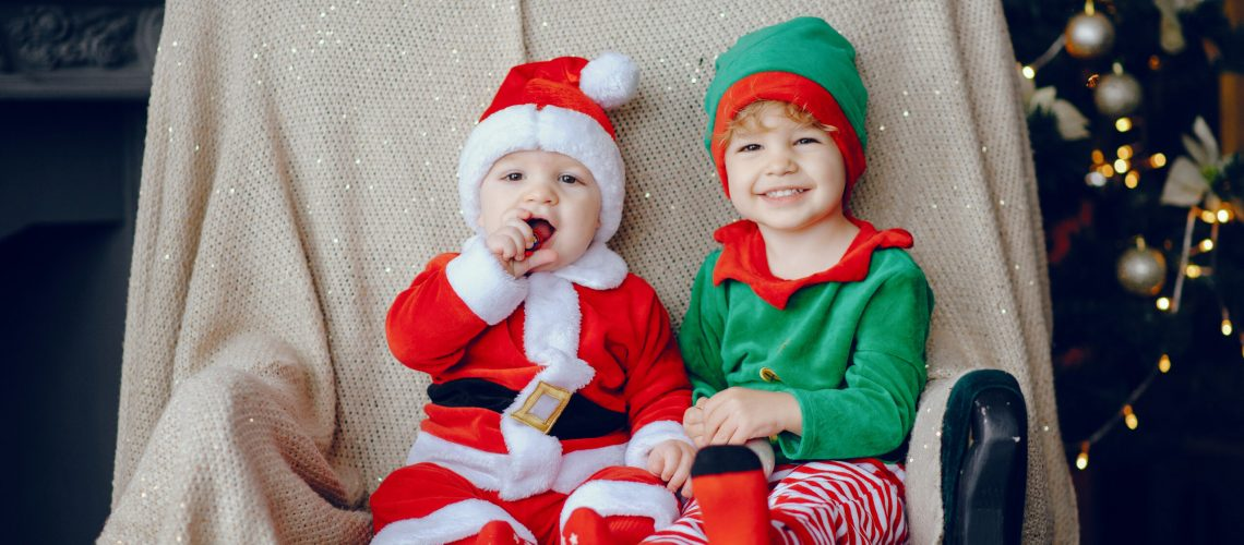 Cute little boys in a christmas costumes. Children by the christmas tree